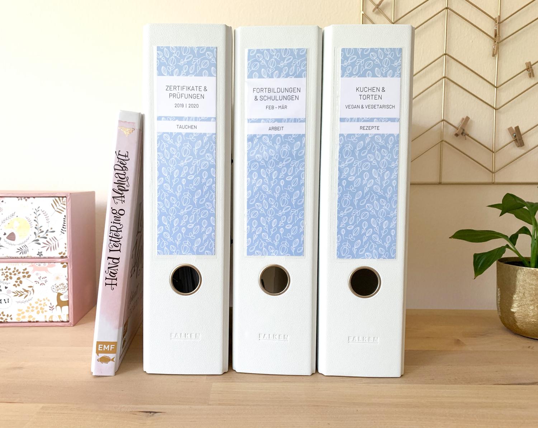 3 weiße Ordner mit Ordneretiketten von Alltagsfreuden in hellblau mit floralem Muster auf einem Sideboard