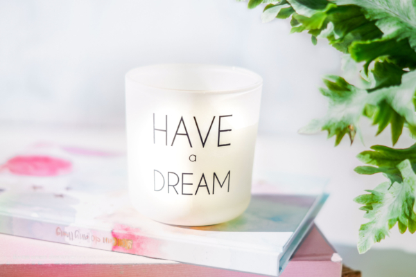 """Windlicht mit der Aufschrift """"Have a dream"""" auf einem Stapel Notizbücher"""